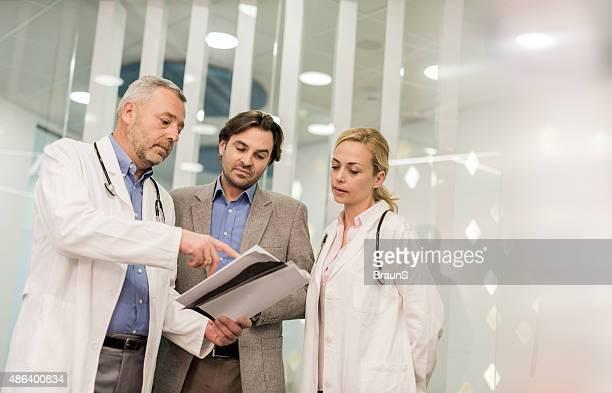 Ärzte Zusammenarbeit mit einem Geschäftsmann bei der Arbeit auf Papierkram.