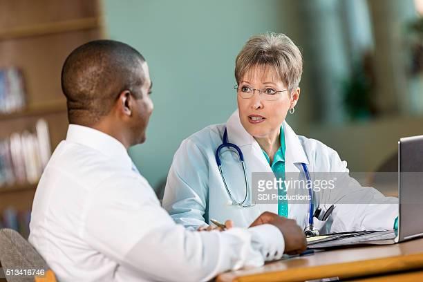 Doctors discuss patient diagnois in staff meeting