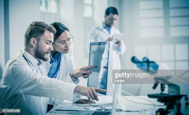 artsen bespreken en wijzend op de x-ray beelden op computermonitor - technicus stockfoto's en -beelden