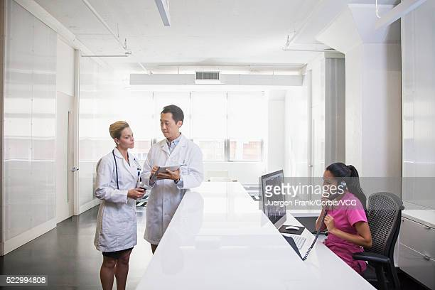 Doctors discussing and receptionist talking on phone