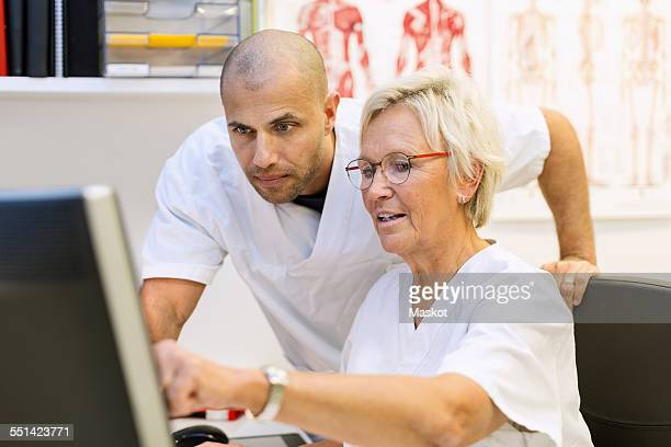 Doctors discussing over computer in office at orthopedic clinic