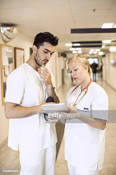 Doctors discussing over digital tablet in hospital corridor