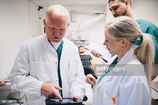 Doctors discussing over digital tablet while patient lying on bed at hospital
