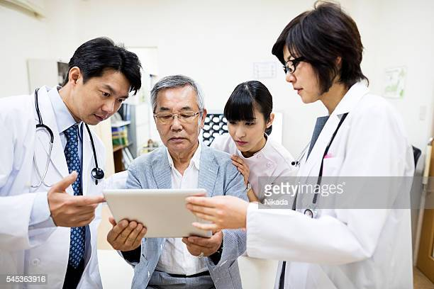 Doctors discussing with senior man while using digital tablet