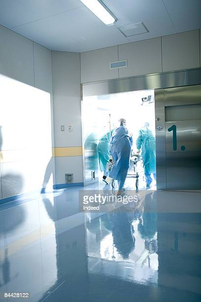 Doctors entering to operating room, rear view