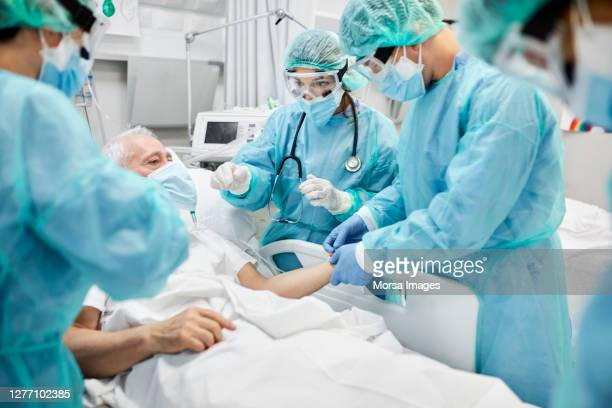 doctors examining coronavirus patient in ward - essential services stock pictures, royalty-free photos & images