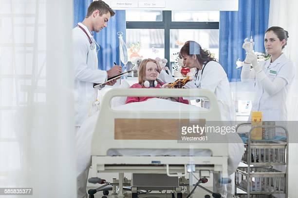 Doctors examining girl in hospital bed