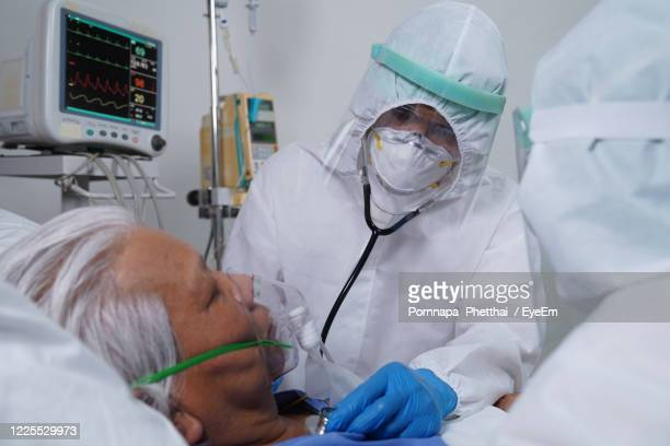 doctors examining senior men in hospital - critical care stock pictures, royalty-free photos & images