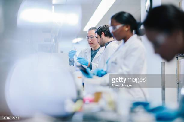 Doctors examining test tubes in laboratory