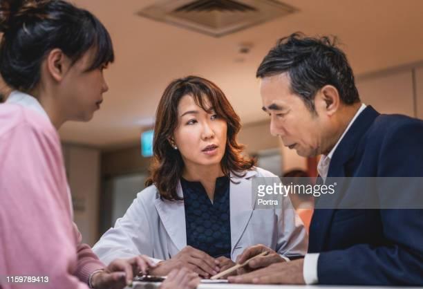 入院患者に報告を説明する医師 - 紙製備品 ストックフォトと画像