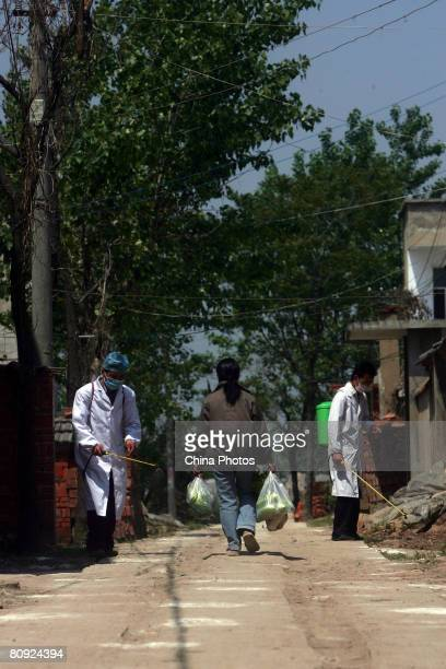 Doctors from local rural hospital disinfects a street of a village on April 29 2008 in the outskirts of Fuyang of Anhui Province east China The...