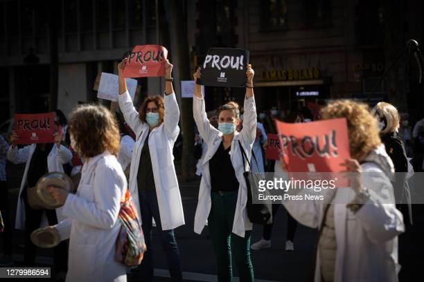 """Doctors from the Primary Care Centres of the Catalan Institute of Health hold up banners reading """"Enough!"""" during a demonstration in Barcelona on..."""