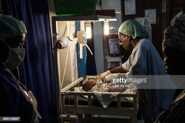 Doctors give emergency treatment to a new born baby whose mother undergoes Caesarean section after she is hospitalized with an infection in Gondama...