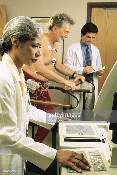 doctors giving stress test to male patient - stress test stock pictures, royalty-free photos & images