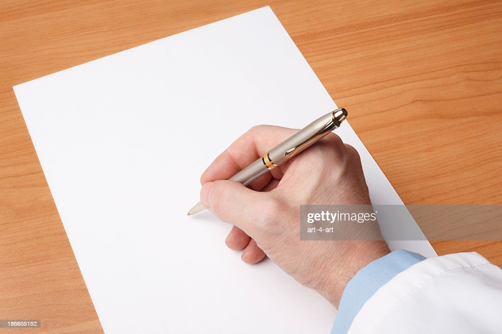 Doctor's hand writing on blank sheet of paper : Stock Photo