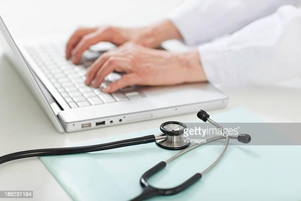 Doctor's hands usando una computadora portátil en el mostrador