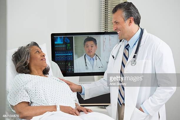 doctors having teleconference with patient in hospital - telemedicine stock photos and pictures