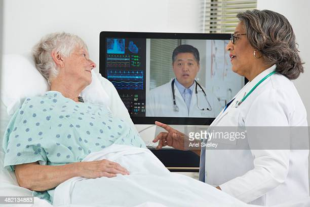 Doctors having teleconference with patient in hospital
