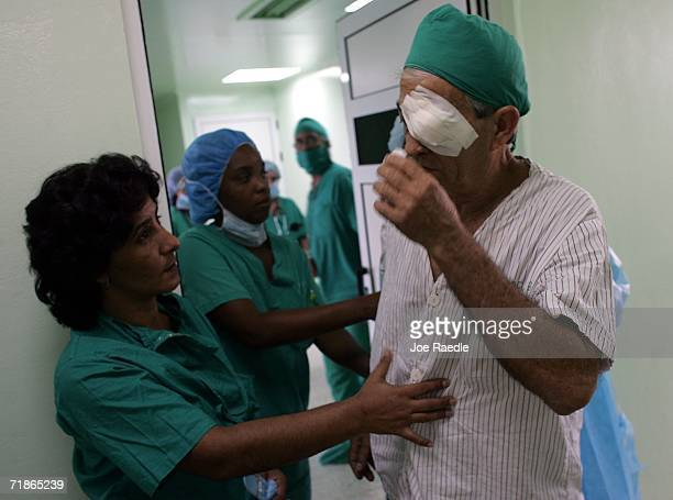 Doctors help a patient after he had eye surgery performed by doctors participating in Operacion Milagro September 12 2006 at Pando Ferrer hospital in...