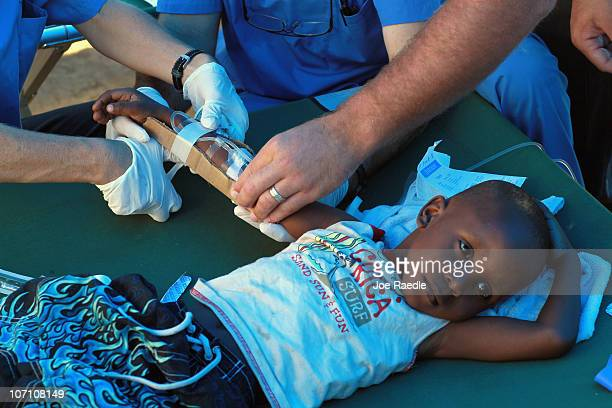 Doctors help Anderson Desir as he lays on a cot while being treated for cholera in a Samaritan's Purse cholera treatment facility on November 24 2010...