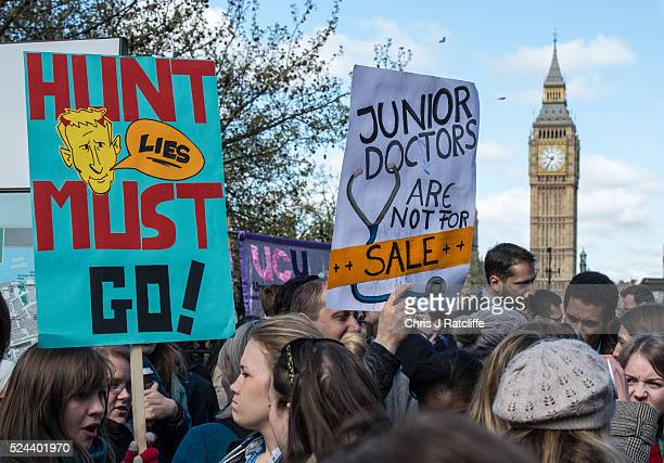 Doctors hold up protest signs whilst striking outside St Thomas' Hospital on April 26 2016 in London England Junior doctors will walk out from 8am to...
