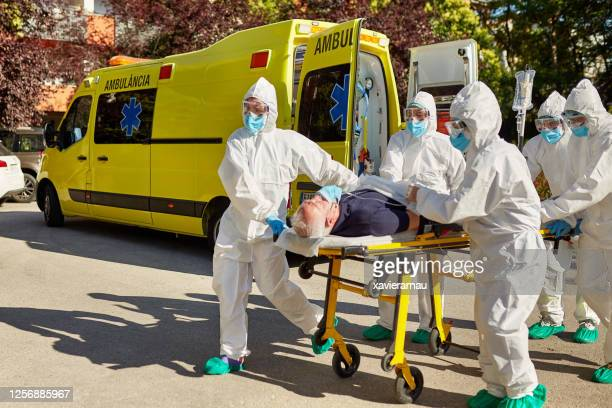 doctors in protective suits moving patient from ambulance - ambulance stock pictures, royalty-free photos & images