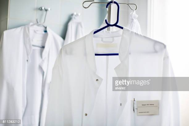 doctor's lab coat on hanger in laboratory - name tag stock photos and pictures