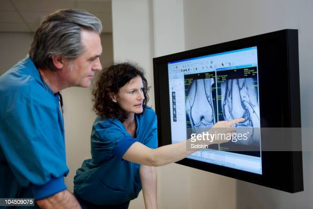 doctors looking at mr image of knee - knees together stock photos and pictures