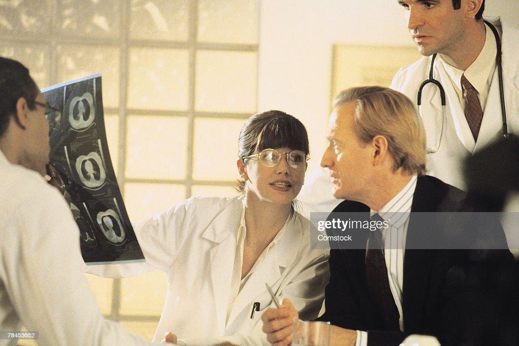 Doctors looking at scan of brain : Stockfoto
