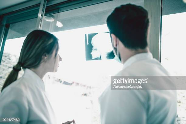 Doctors Looking At X-Ray Image Of Patient And Making Diagnosis