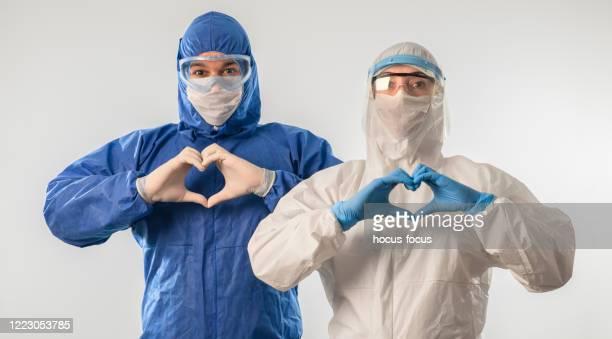 doctors making heart shape and sending love during coronavirus covid 19 novel corona virus outbreak - helmet visor stock pictures, royalty-free photos & images