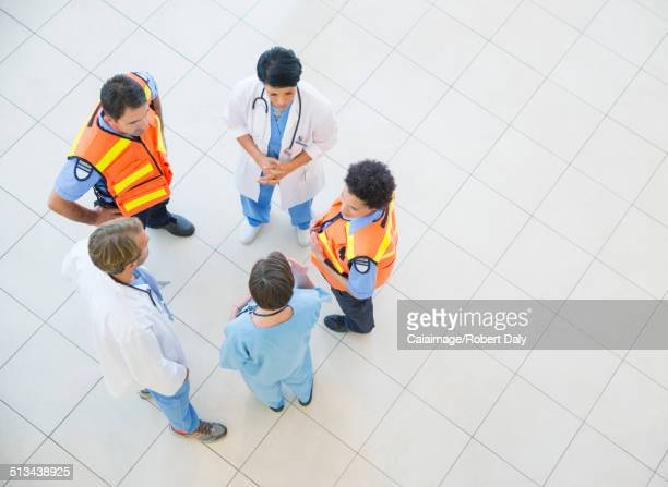 Doctors, nurses, and paramedics talking in hospital
