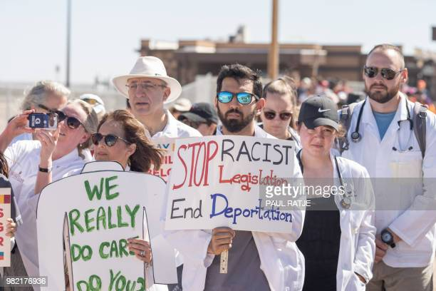 Doctors, nurses, medical students hold up posters June 23, 2018 at the Tornillo Port of Entry in Tornillo, Texas, to demand quick reunification of...