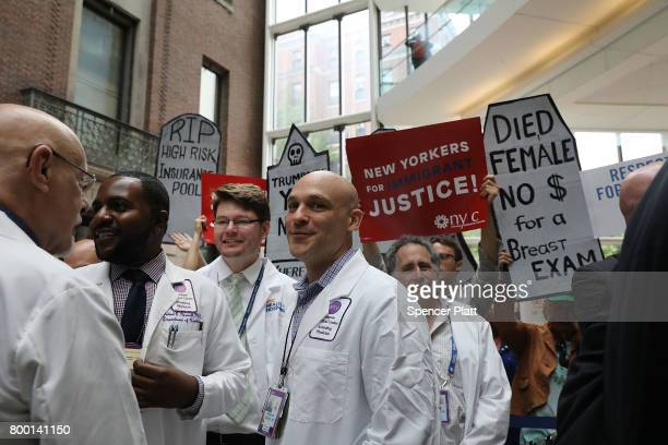Doctors nurses patients and activists listen as Senate Minority Leader Chuck Schumer speaks at Bellevue Hospital a day after the Republicans released...