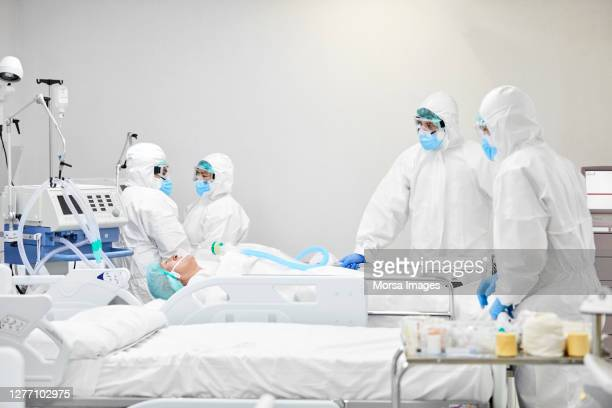 doctors operating senior patient in hospital during covid-19 - oxygen mask stock pictures, royalty-free photos & images