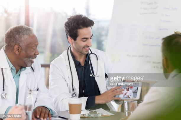 doctors participate in video conference with colleague - telemedicine stock photos and pictures