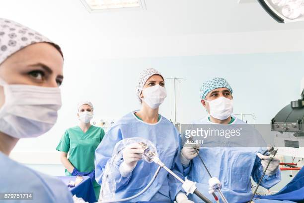 doctors performing surgery in operating theater - laparoscopic surgery stock photos and pictures