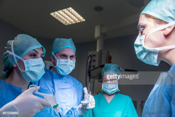 doctors performing surgery in operating theater - laparoscopy stock photos and pictures