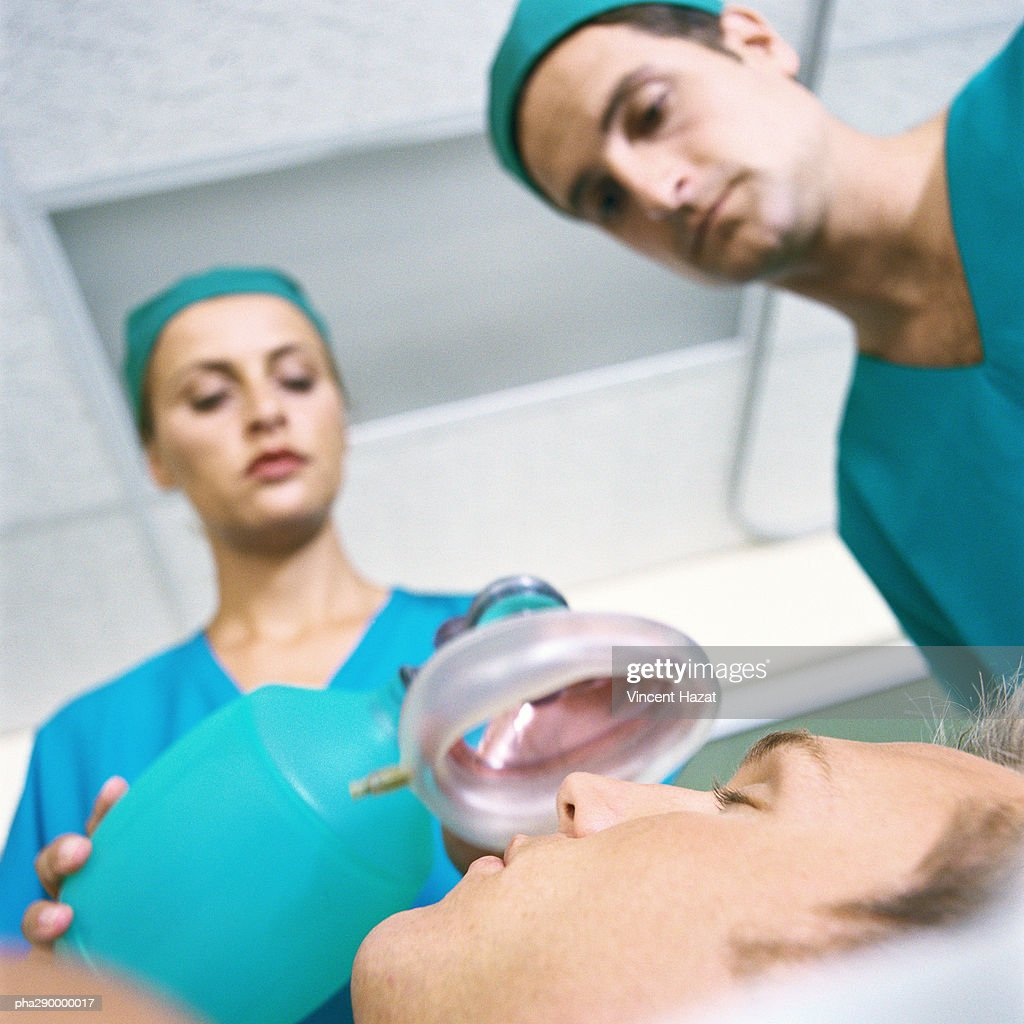 Doctors placing oxygen mask over patient's face : Stockfoto