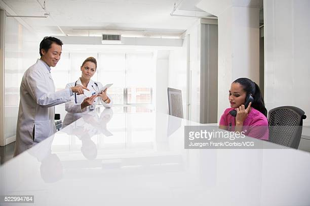 Doctors reading tablet with receptionist on telephone