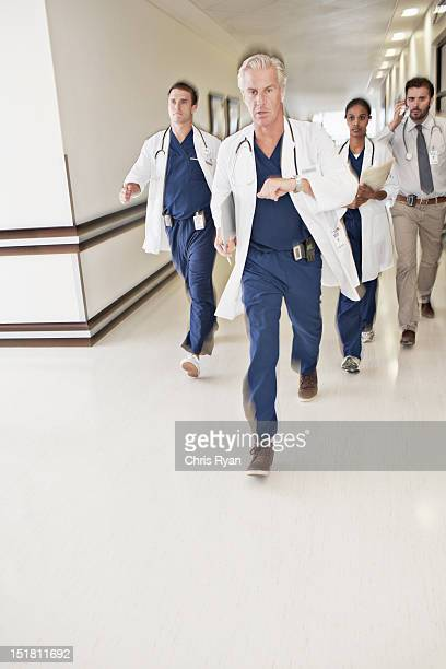 doctors rushing down hospital corridor - mid adult stock pictures, royalty-free photos & images