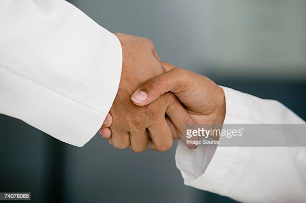 doctors shaking hands - long sleeved stock pictures, royalty-free photos & images
