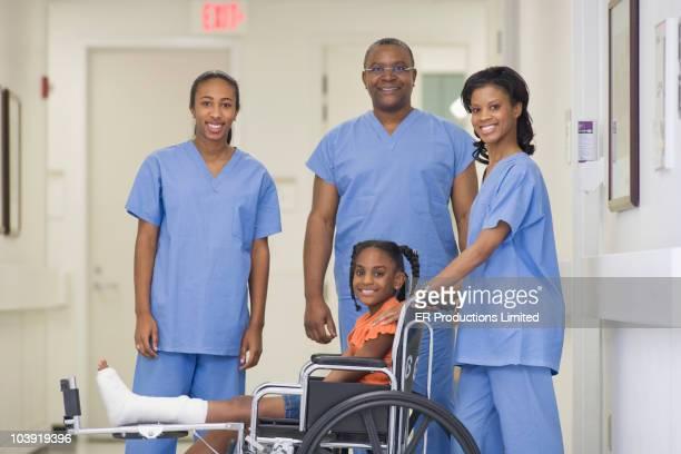 Doctors standing with girl with broken leg