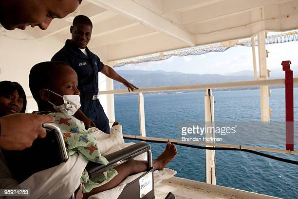 Doctors take a sixyearold Haitian boy who suffered a broken left leg during the recent earthquake out on the deck of the USNS Comfort a US Naval...