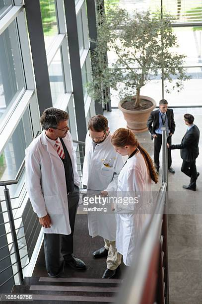 Doctors talking on staircase in office