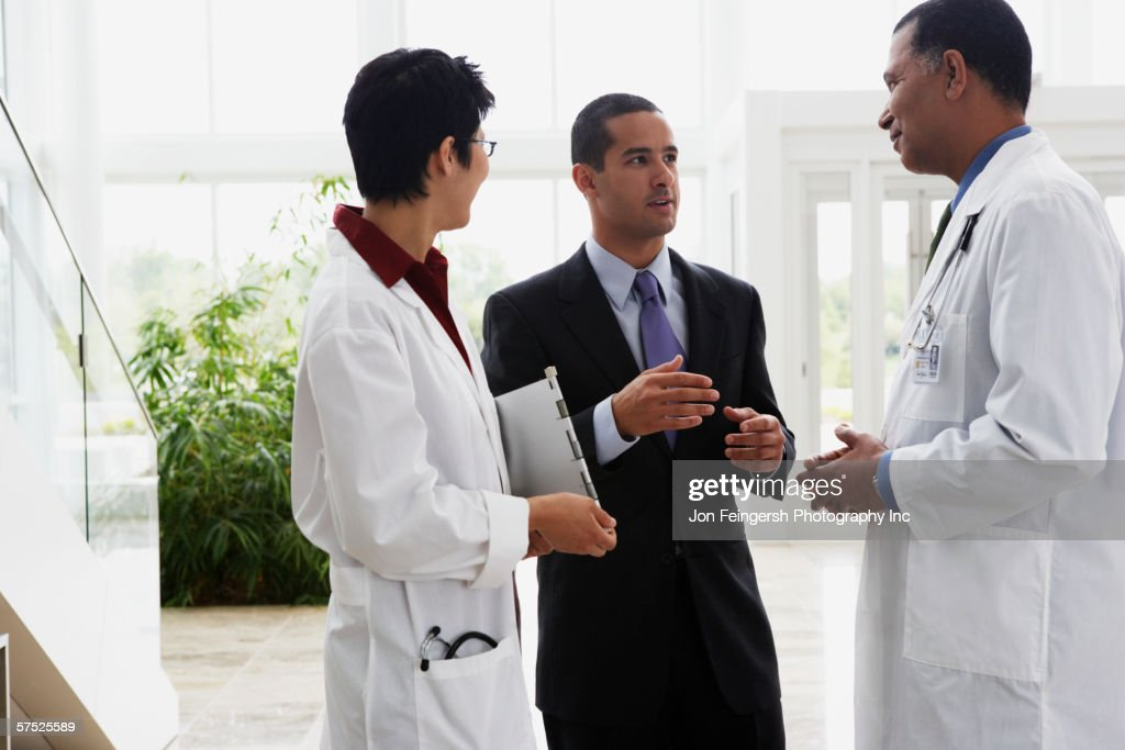 Doctors talking to businessman : Stock Photo