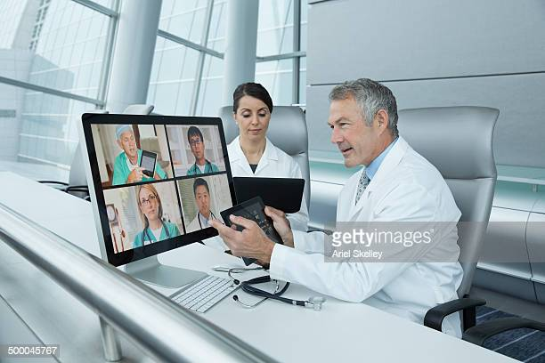 Doctors teleconferencing in office