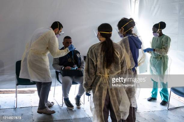 Doctors test hospital staff with flulike symptoms for coronavirus in setup tents to triage possible COVID19 patients outside before they enter the...