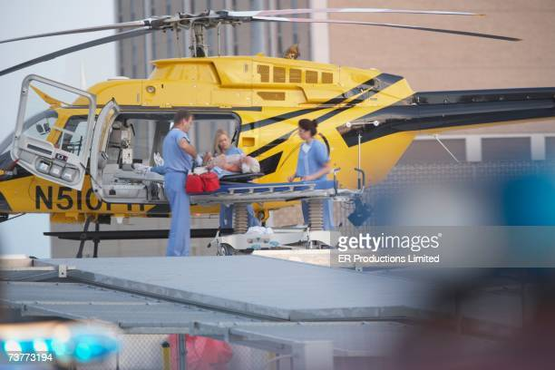 doctors unloading patient from medical helicopter - helicopter emergency foto e immagini stock