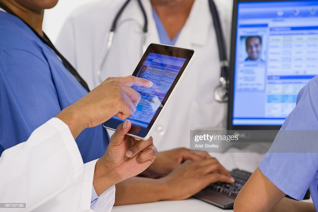 Doctors using digital tablet together in hospital : Stock Photo